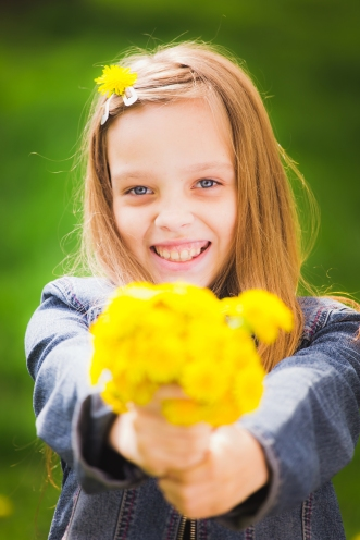 Close up portrait of smiling young girl holding bouquet of flowers in hands. Girl with yellow dandelions. Smiling face of teenager with long hear. Vertical color photo.